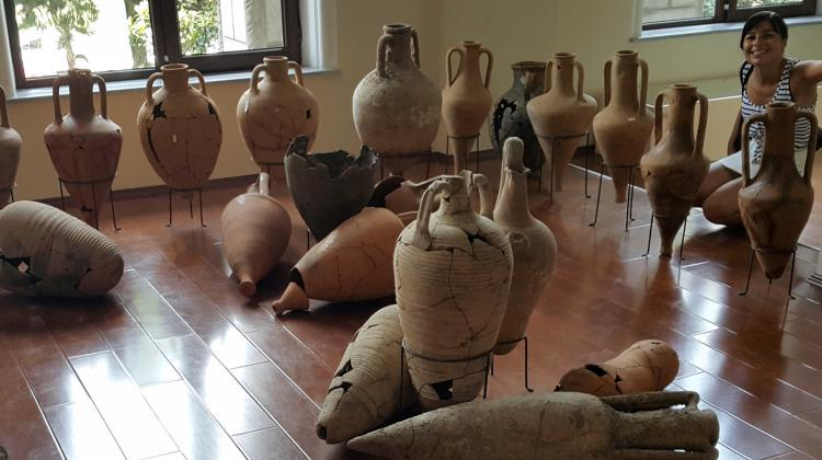 The author of the project surrounded by amphorae from the eastern part of the Mediterranean, Archaeological Museum in Batumi. Photo by M. Marciniak