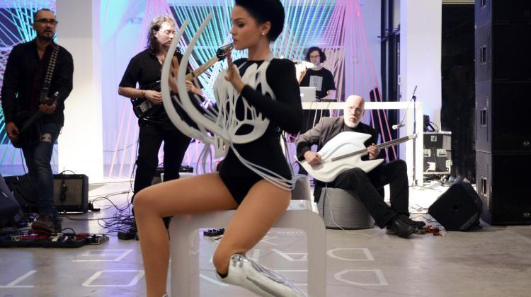 Viktoria Modesta performs dressed in 3D printed interactive sound corset and 'fangs'. Her prosthesis and shoes are also 3D printed. The artist is accompanied by a band playing 3D printed instruments. Copyright: Sonic Bustier by MONAD Studio with Viktoria Modesta and Anouk Wipprecht.